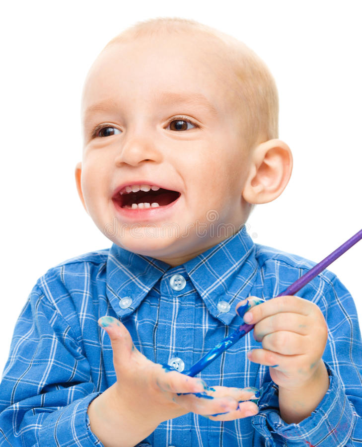 Little boy is playing with paints. Portrait of a cute little boy playing with paints, isolated over white royalty free stock photos