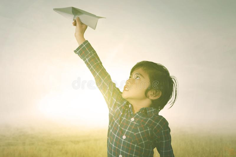Little boy playing a paper airplane in the park. Picture of a little boy playing a paper airplane in the park with sunlight background royalty free stock photography