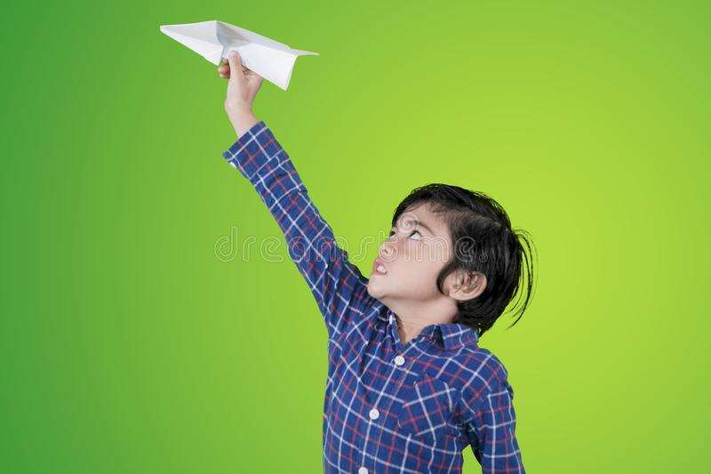 Little boy playing a paper airplane on studio. Picture of a little boy playing a paper airplane in the studio with green screen background royalty free stock photo
