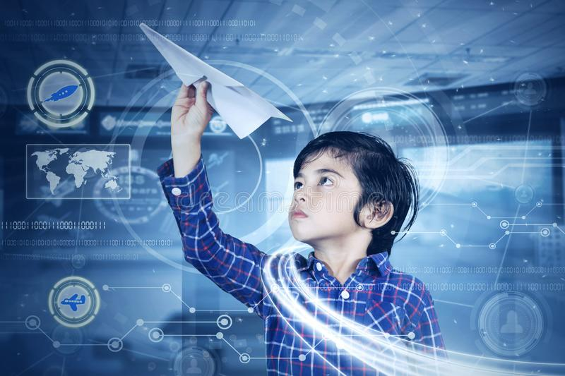 Little boy playing a paper plane with virtual screen. Picture of a little boy playing a paper airplane with virtual screen background stock image