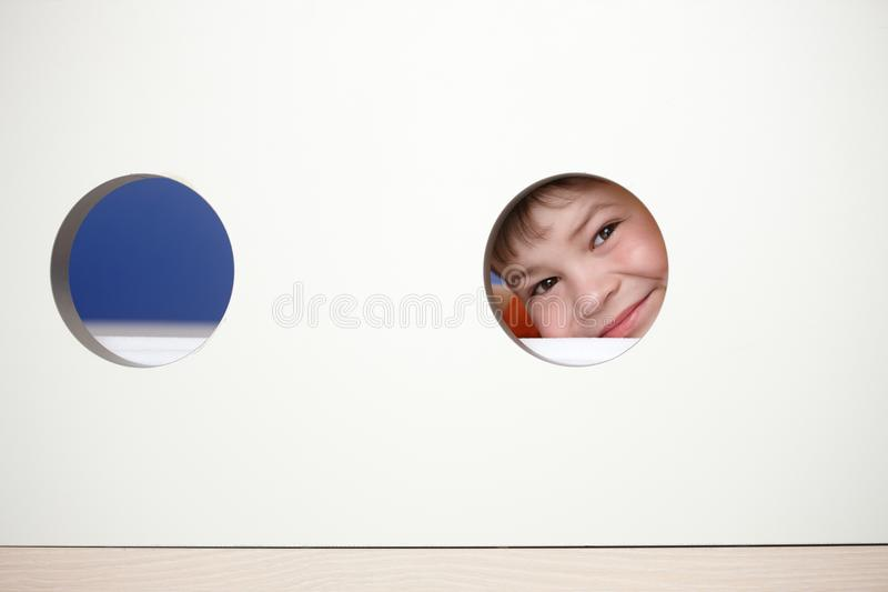 Little boy playing peek-a-boo smiling. Little boy peeping, playing peek-a-boo, smiling royalty free stock photo