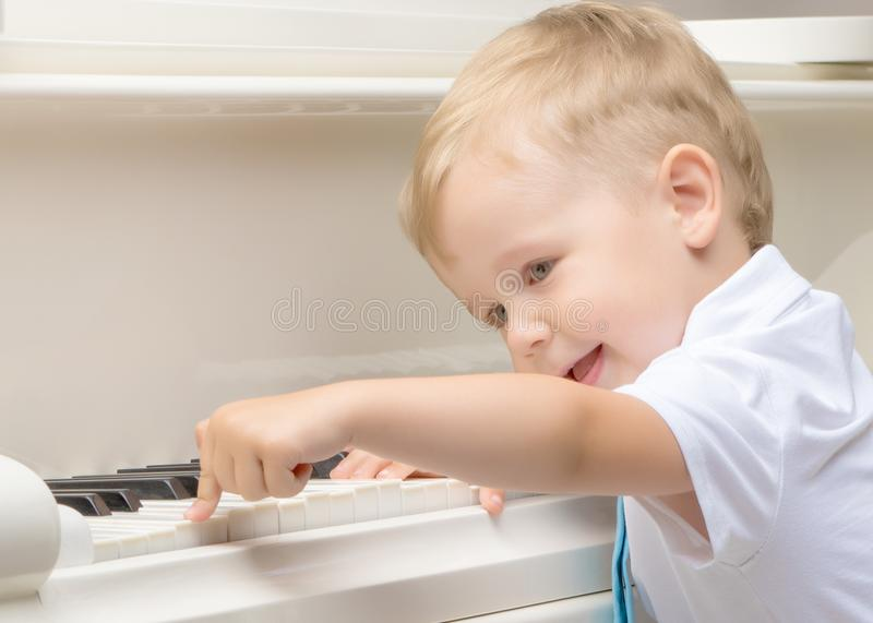 Little boy playing the piano stock image