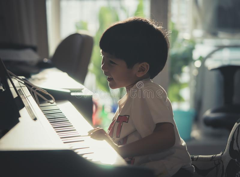 Little Boy playing with piano and Music Tablet at home royalty free stock photo
