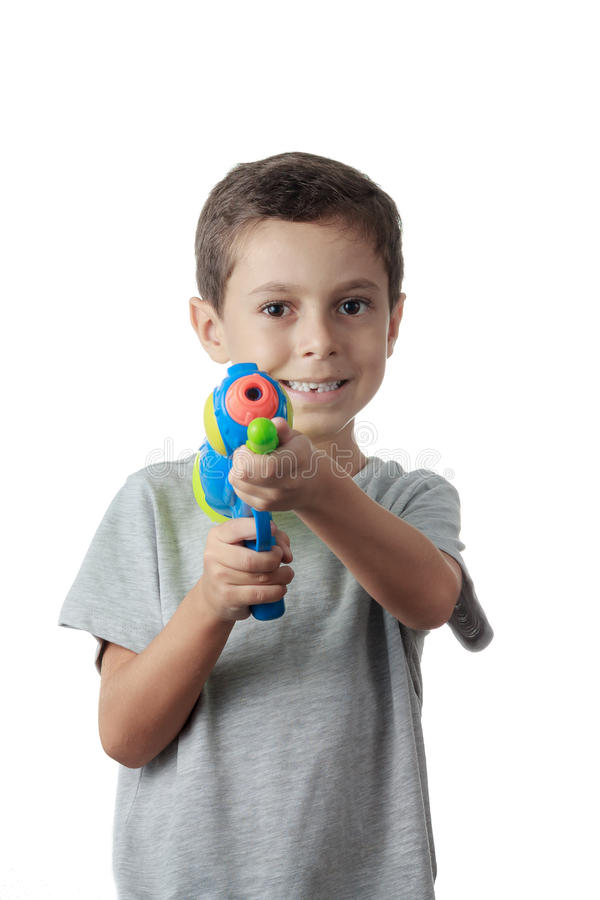 Little boy playing with plastic water gun. Isolated on white stock image