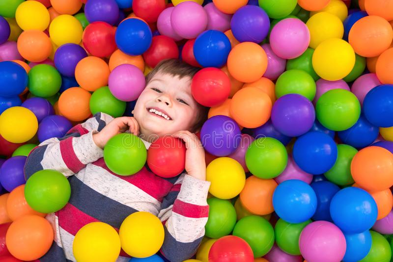 Little boy playing in the pool with plastic balls in the nursery. Indoors activities for children. Development of stock image