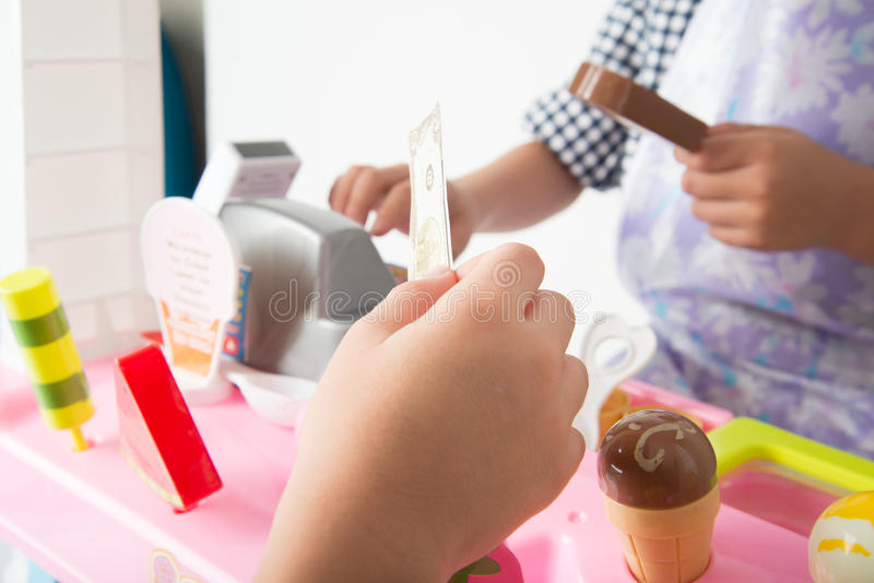 Little boy playing pretend as a saler in icecream shop store stock images