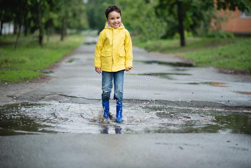 Little boy playing in puddle stock images