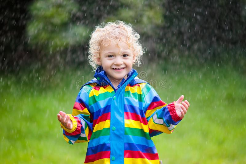 Little boy playing in the rain. Little blond curly boy in a waterproof jacket in rainbow color playing in the rain. Kids having fun outdoors in autumn shower stock photography