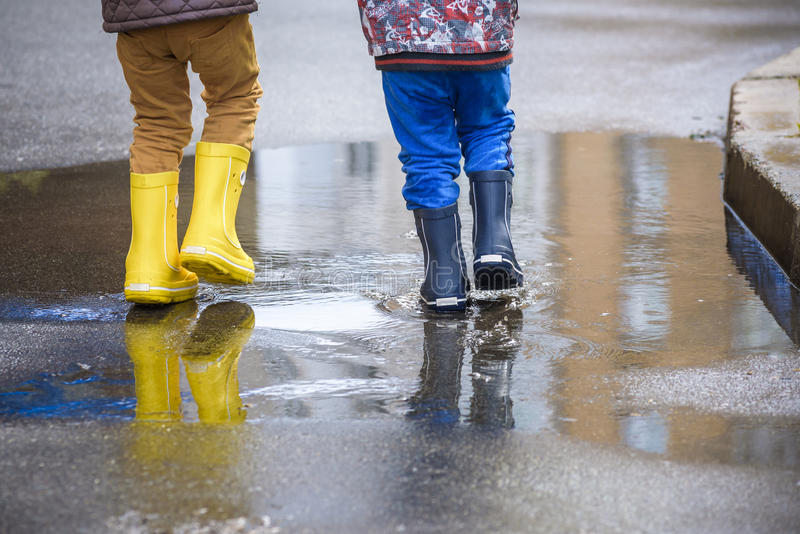 Little boy playing in rainy summer park. Child with colorful rainbow umbrella, waterproof coat and boots jumping in puddle and mud. In the rain. Kid walking in stock image