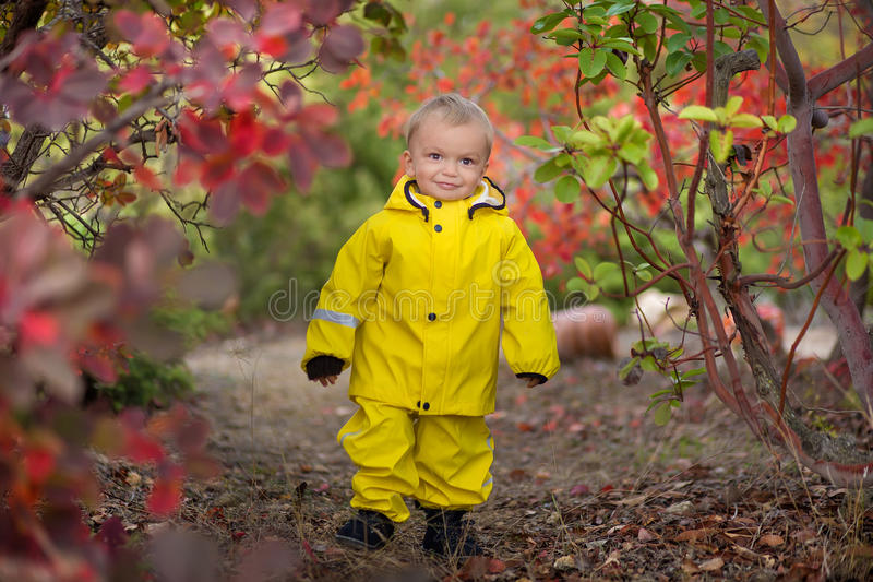 Little boy playing in rainy summer park. Child with colorful rainbow umbrella, waterproof coat and boots jumping in royalty free stock photo