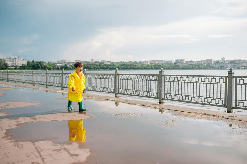 Little boy playing in rainy summer park. Child with umbrella, waterproof coat and boots jumping in puddle and mud in the rain. Kid stock photo