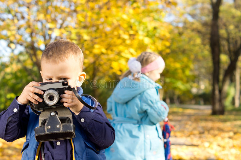 Little boy playing with a retro camera royalty free stock image