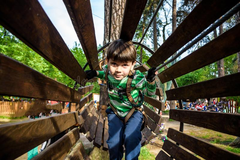 Little boy playing at rope adventure park. Summer holidays concept. Cute child having fun in net tunnel. Modern amusement park for stock photos