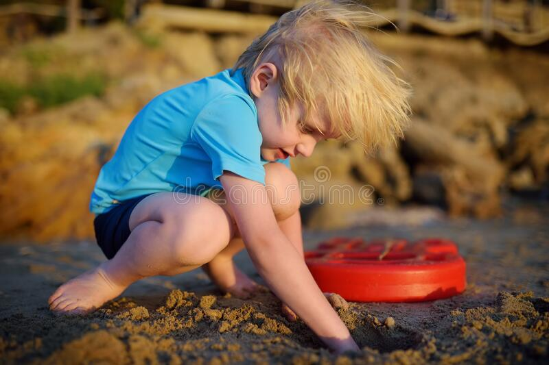 Little boy playing on sand beach near seashore in Greece stock images