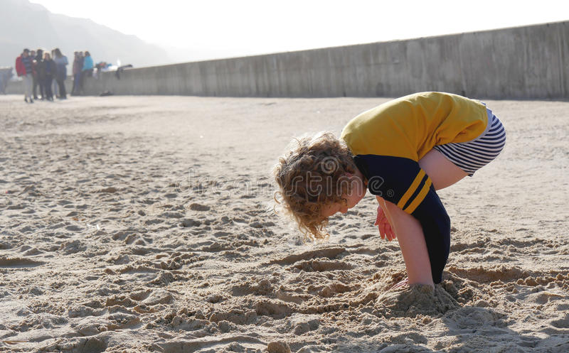 Little boy playing in the sand. Little blond boy playing in the sand royalty free stock image