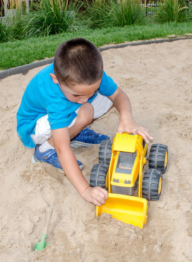 Little boy playing in the sand. A cute little hispanic boy plays in the sand with a toy front end loader stock images