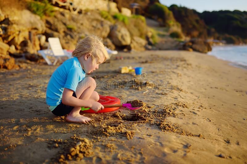 Little boy playing with shovel on sand beach near seashore in Greece stock photography
