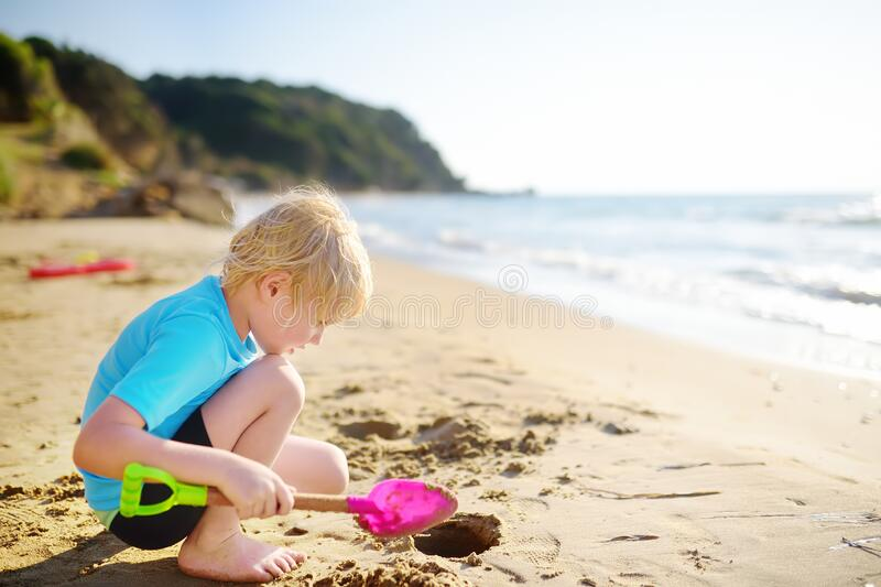 Little boy playing with shovel on sand beach near seashore in Greece royalty free stock image