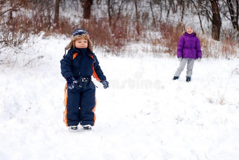 Little boy and girl walk in a snowy garden stock photos