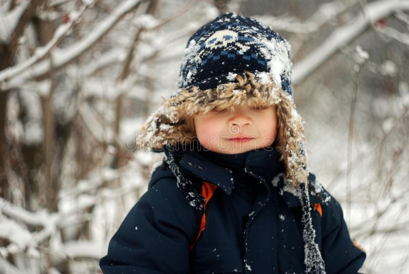 Little Boy Playing In The Snow stock photo