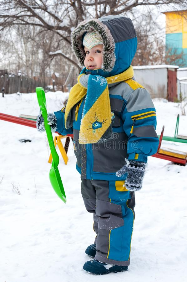 Little boy playing with snow and spade royalty free stock images