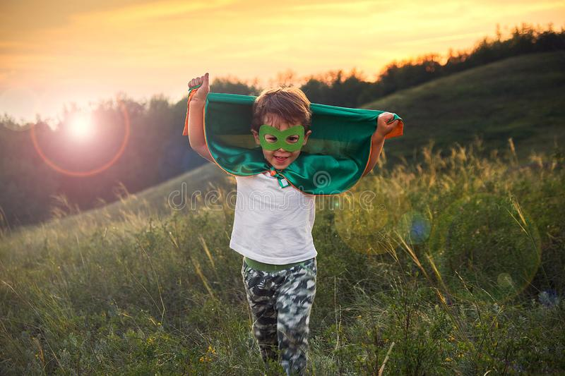 Little boy playing a superhero. Kid in an Superhero`s costume. happy child runs to meet the photographer. royalty free stock image