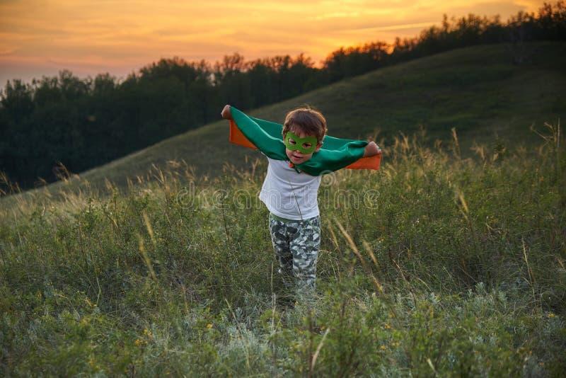 Little boy playing a superhero. Kid in an Superhero`s costume. happy child runs to meet the photographer. stock photo