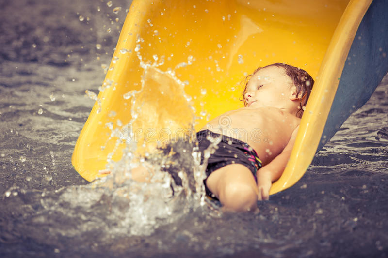 Little boy playing in the swimming pool on slide. At the day time stock photos