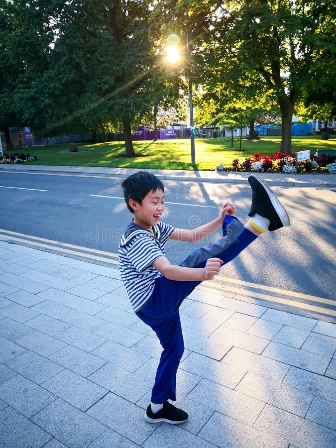 The little boy is playing tae kwon do under the sunshine. royalty free stock photo