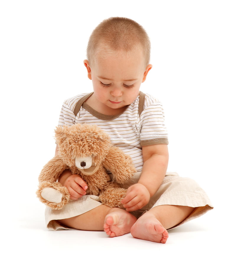 Little boy playing with toy bear royalty free stock images