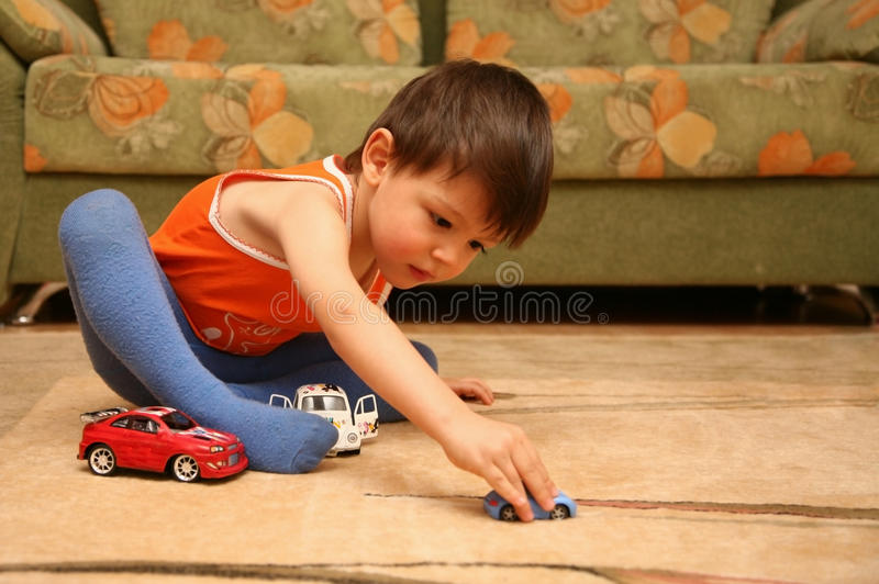 Little Boy With Toy Car : Little boy playing toy cars on the floor stock photo