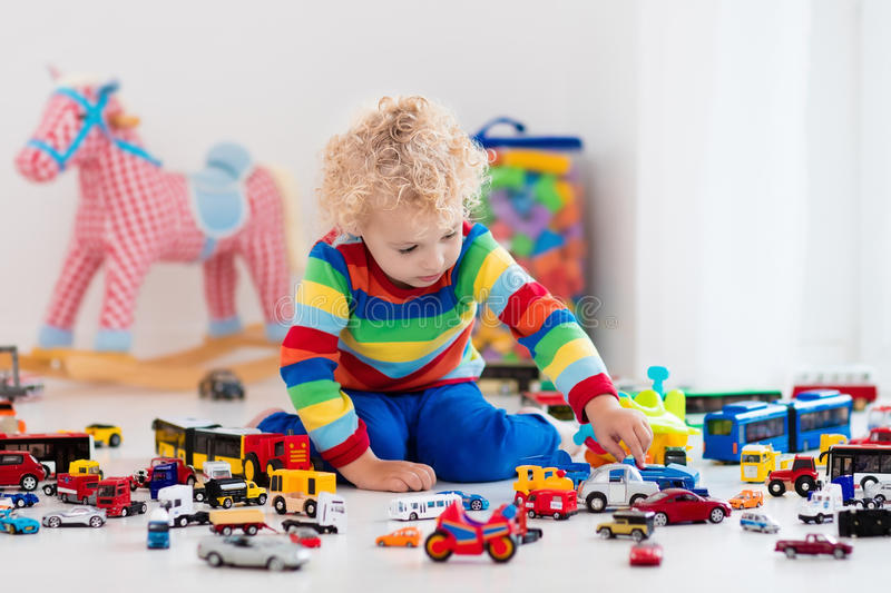 Little boy playing with toy cars stock images