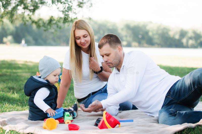 Little boy playing toy cars and having fun with his father and mother outdoors stock images