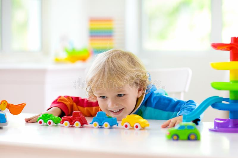Boy playing toy cars. Kid with toys. Child and car. Little boy playing toy cars. Young kid with colorful educational vehicle and transport toys. Child driving royalty free stock photography
