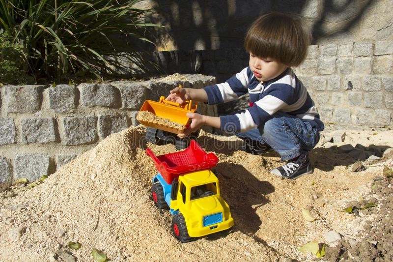 Little boy playing with toy digger and dumper truck. stock image