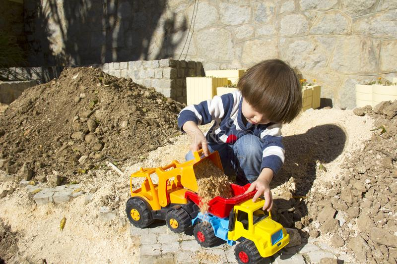 Little boy playing with toy digger and dumper truck. stock photo