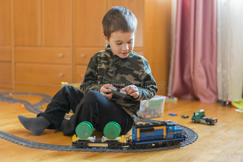 Little boy playing with a toy railway. Little boy playing with railway lying on the floor. Joyful emotions.  stock photos