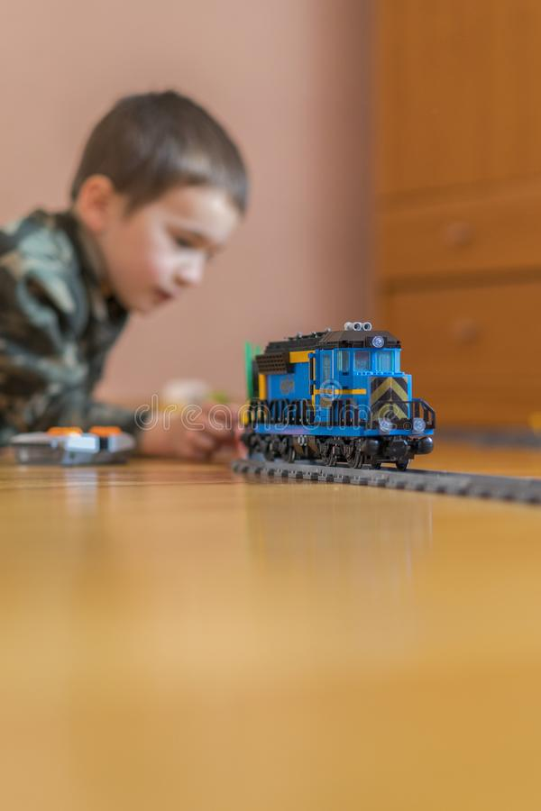 Little boy playing with a toy railway. Little boy playing with railway lying on the floor. vertical photo.  stock images