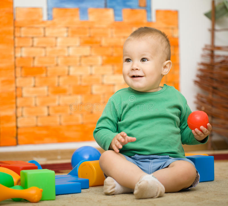 Little boy is playing with toys in preschool. While sitting on floor royalty free stock photography
