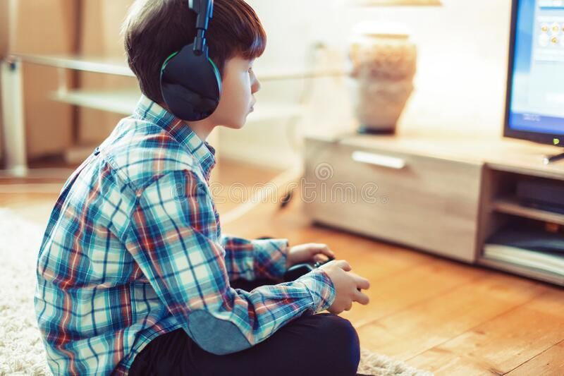 Little boy playing video game by controller side view royalty free stock photo