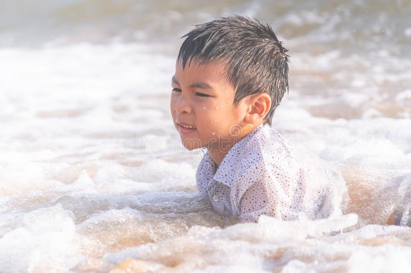 Little boy playing with wave and sand on Pattaya beach royalty free stock image
