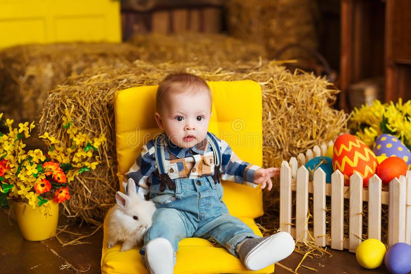 Little boy playing with white rabbit and carrot indoor. Spring easter fun for children. Happy childhood concept. stock image