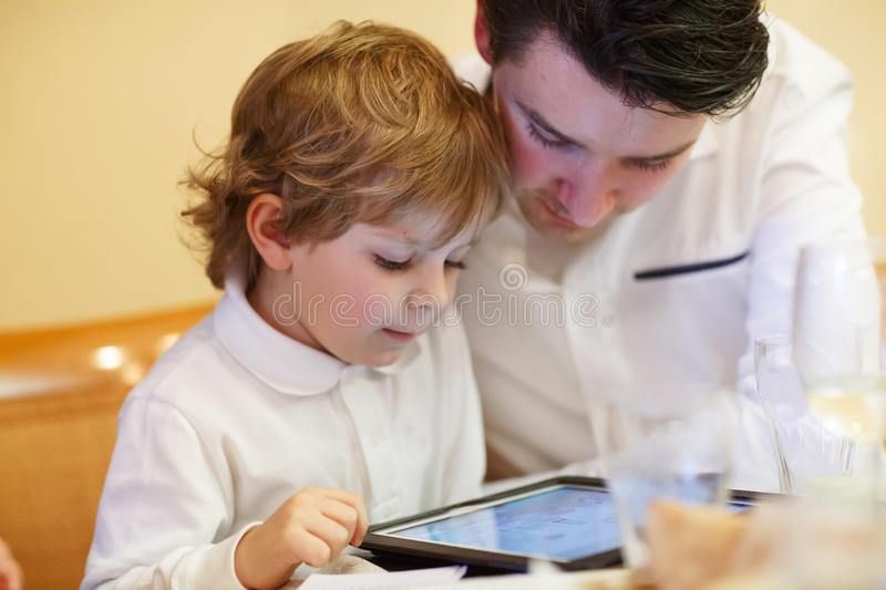Little boy playing wih his older brother with tablet pc royalty free stock photography