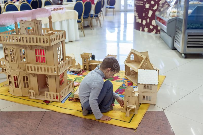 Little boy playing wooden constructor in the pavilion of the exhibition hall at the popular traditional fair of handmade folk arts stock image
