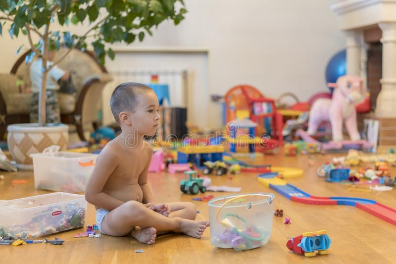 Little boy in the playroom with toys. room full of toys. Lots of toys, many cars piled on the floor royalty free stock photos