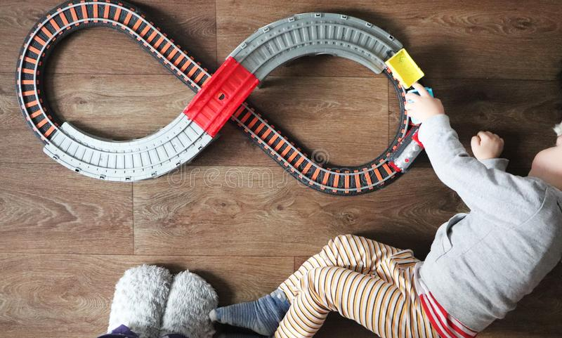 A little boy plays a children`s railway. Mom is watching her son from above. The child is fascinated by the train stock image