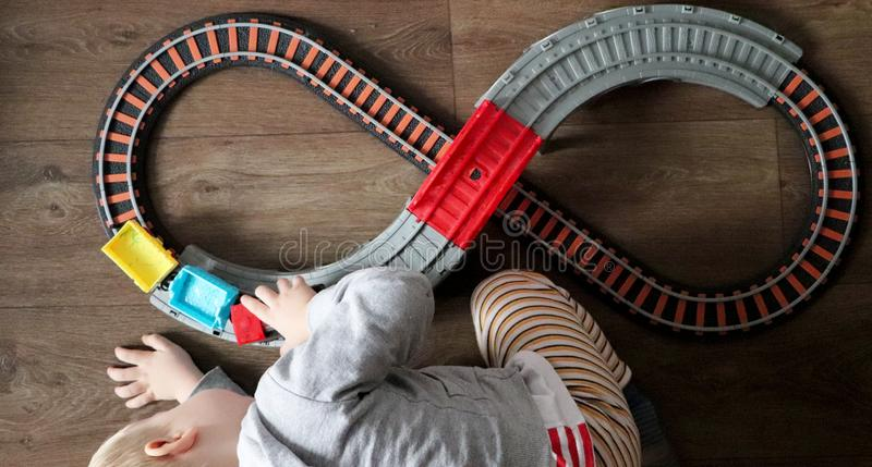 A little boy plays a children`s railway. Mom is watching her son from above. The child is fascinated by the train stock images