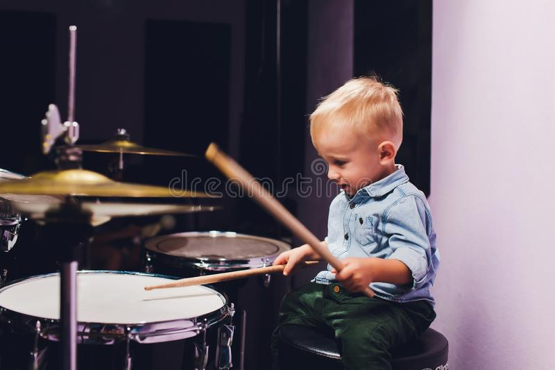 Little boy plays drums in recording studio. stock images