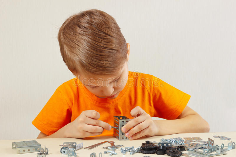 Little boy plays with metal constructor at table stock photos