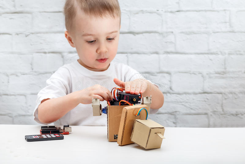 Little boy plays with the robot. Child collects a robot sitting at the table stock photography